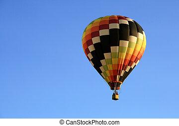 Multicoloured hot air balloon in the blue sky.