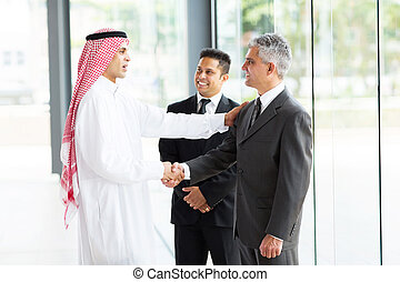 multicultural business partners handshaking in office