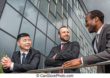 multicultural business team meeting outdoors near office building, successful businessmen concept