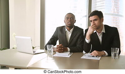 Multicultural businessmen conducting job interview, asking questions to female applicant