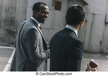 multicultural businessmen holding coffee cup and walking outdoors, business people team concept