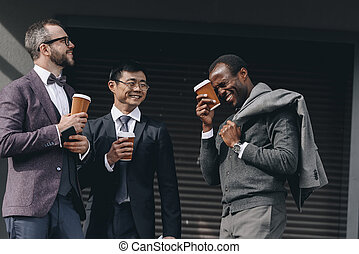 multicultural businessmen holding paper coffee cups and standing outdoors, business people team concept