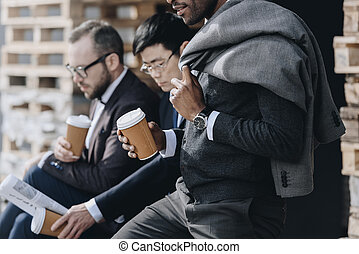 multicultural businessmen holding paper coffee cups and sitting outdoors, business people team concept