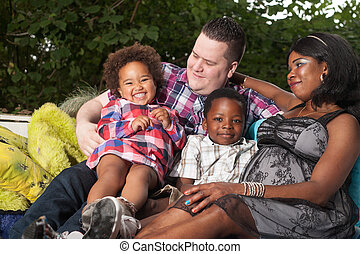 Multicultural family on the couch - African family is...