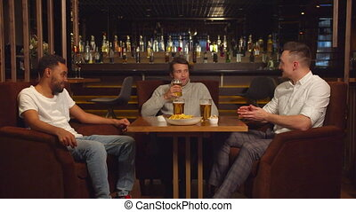 Multicultural friends sit at the bar, drink beer, talk and laugh