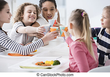 Multicultural group of children toasting during birthday party at home