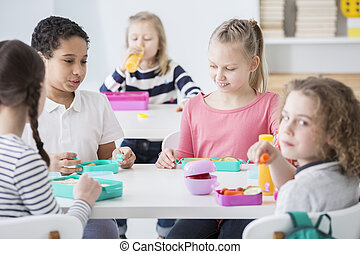 Multicultural group of kids eating lunch at school
