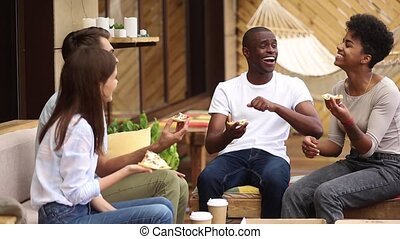 Multicultural happy friends laughing eating pizza in restaurant outdoor