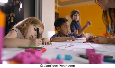 Multicultural kids enjoying drawing at art lesson
