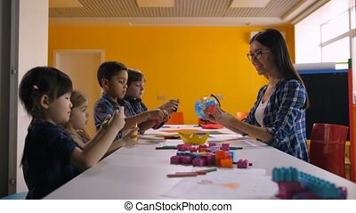 Multicultural kids making ship with colored paper - Cheerful...