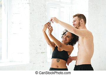 Multicultural young sport couple using mobile phone while standing