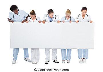 multiethnic, équipe soignant, regarder, vide, panneau affichage