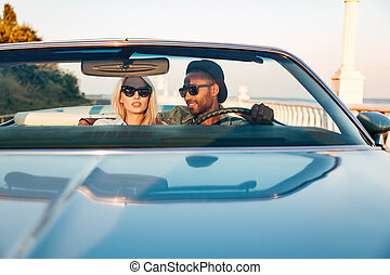 Multiethnic beautiful young couple driving car