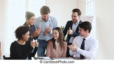 Multiethnic business team congratulate happy female worker applaud in office