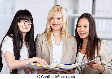 Multiethnic Businesswomen Holding Binder In Office