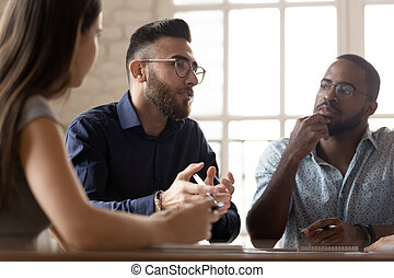 Serious multiethnic businesspeople gather at team briefing brainstorm over startup project together, diverse employees talk consider business ideas share thoughts at meeting, collaboration concept