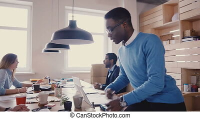 Multiethnic colleagues talk in modern office. Young happy friendly business people talk, show gestures during break 4K.