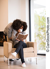 multiethnic couple hugging in front of fireplace