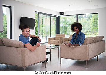 multiethnic couple in living room - Young multiethnic couple...