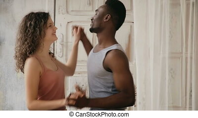 Multiethnic couple in pajamas dancing in the morning. Man and woman spending morning at home together.