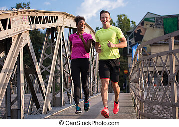 multiethnic couple jogging in the city