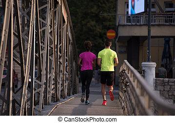 multiethnic couple jogging in the city