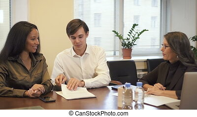 Multiethnic couple signing mortgage contract in realtor office.