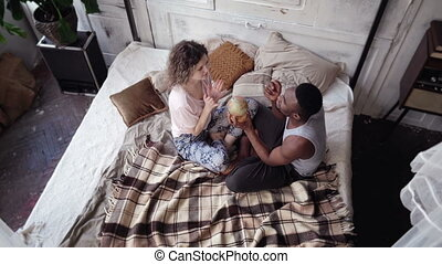 Multiethnic couple sit on the bed and twist the globe. Man and woman pick the destination to travel, hug and kiss.