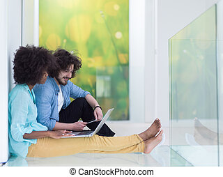 multiethnic couple using a laptop on the floor