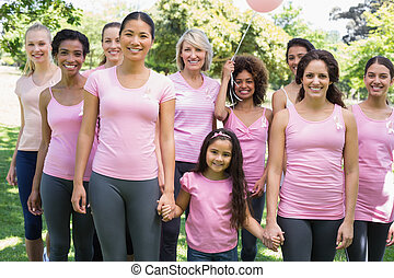 Multiethnic females supporting breast cancer awareness -...