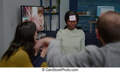 Multiethnic friends having attaching sticky notes on forehead while playing guess who game. Mixed race people having fun, laughing together while sitting on sofa in living room late at night