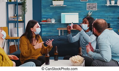 Thoughtful multiethnic friends with sticky notes on foreheads playing name game wearing face mask keeping social distancing preventing covid19 spread drinking beer enjoying popcorn. Conceptual image.
