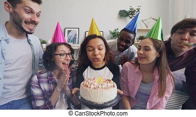 Multiethnic group of friends celebrating birthday singing...