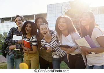 Multiethnic group of young cheerful students standing outdoors