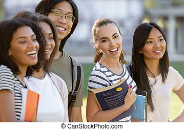 Multiethnic group of young happy students standing outdoors.