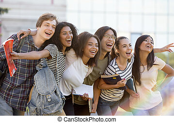 Multiethnic group of young happy students standing outdoors