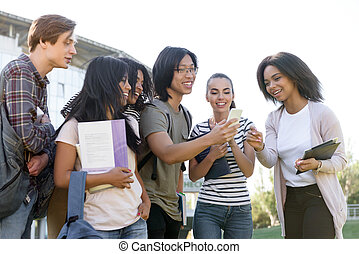 Multiethnic group of young happy students using mobile phone