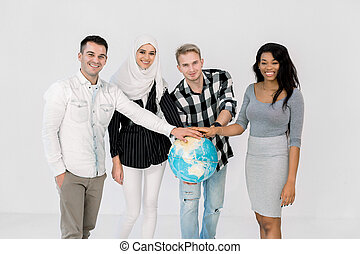 multiethnic group of young people holding hands on the Earth globe and standing isolated on white background. Earth day. Green concept