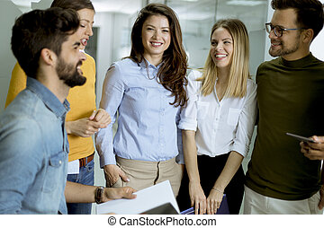 Multiethnic group of young people standing in the modern office and brainstorming