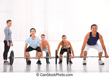 Multiethnic group with weightlifting bar workout in fitness cent