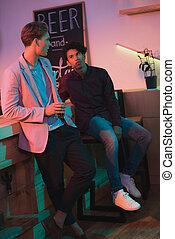 multiethnic men having conversation in bar - multiethnic men...