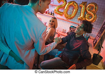multiethnic men shaking hands during new year celebration in...
