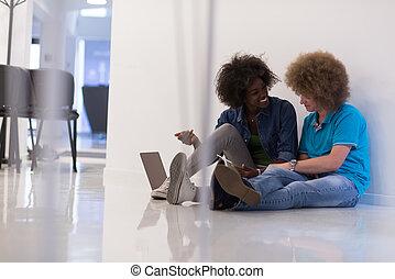 multiethnic, paar, sitzen boden, mit, a, laptop, und, tablette