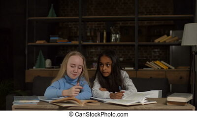 Multiethnic school girls studying together at home