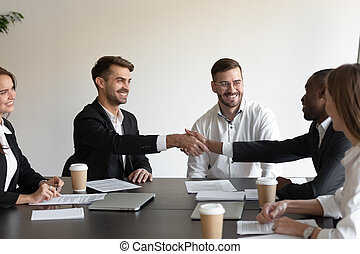 Multiethnic smiling colleagues handshake get acquainted at meeting
