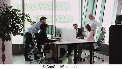 Multiethnic staff using computers talking in big office