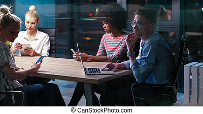 Multiethnic startup business team in night office -...