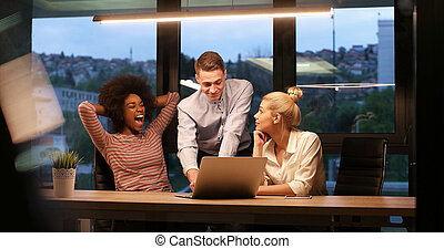 Multiethnic startup business team in night office -...