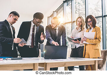 Multiethnic startup business team on meeting in modern light office interior brainstorming, working on laptop and tablet. Group of Multiethnic Diverse Busy Business People Concept
