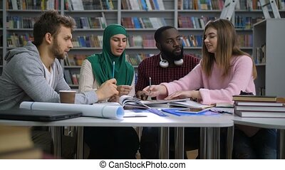Multiethnic students preparing to exams in library